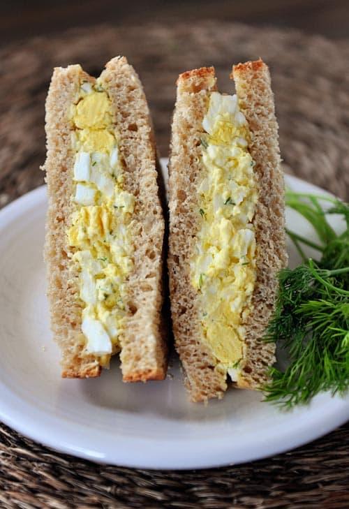 an egg salad sandwich cut in half on a white plate
