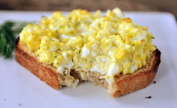 open faced egg salad sandwich with a bite taken out on a white plate