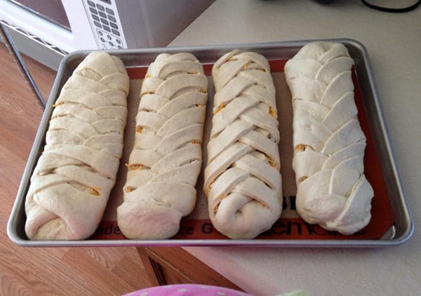 four uncooked braided breads on a cookie sheet