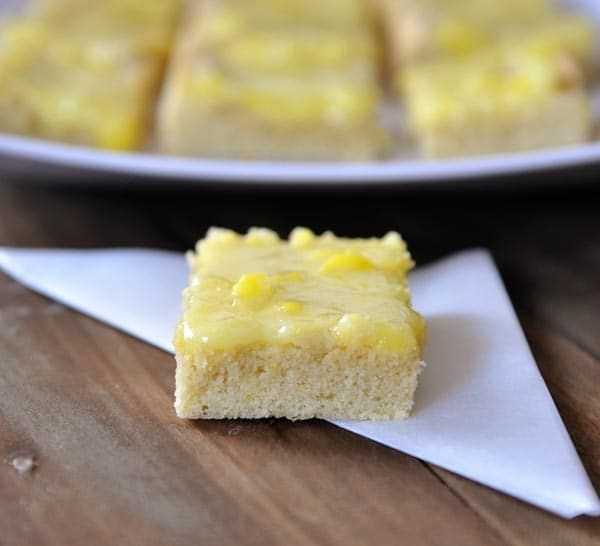 a lemon bar with lemon drops on top in front of a tray of more lemon drop bars