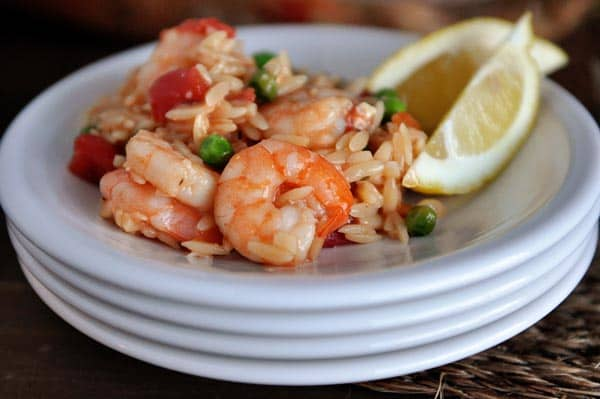 a stack of white plates with a helping of shrimp and orzo and two lemon slices on the side