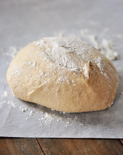 Uncooked pizza dough dusted with flour, laying on a piece of parchment paper.