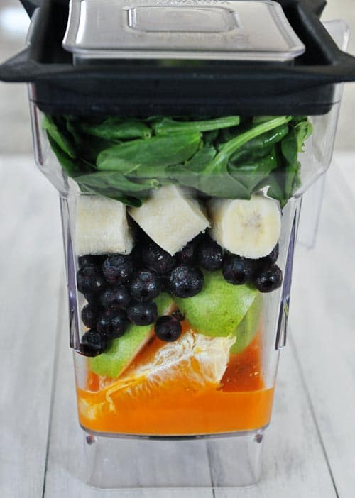A blender with layers of orange juice, pears, blueberries, bananas, and spinach.