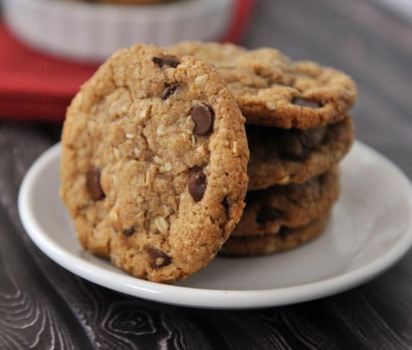 a white plate with stacked chocolate chip cookies and one laying on it's side on the stack