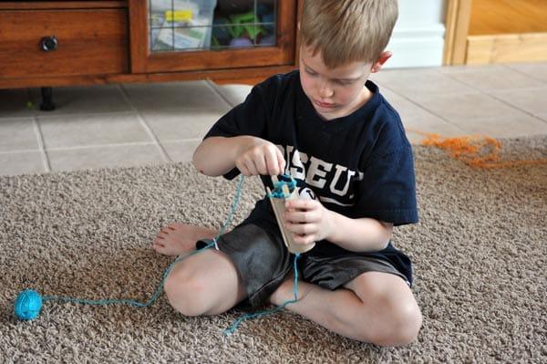A little boy doing a craft.