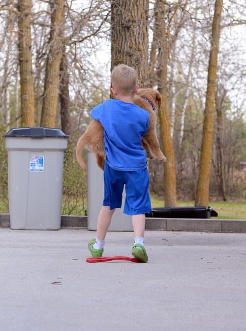 A little boy holding a puppy.