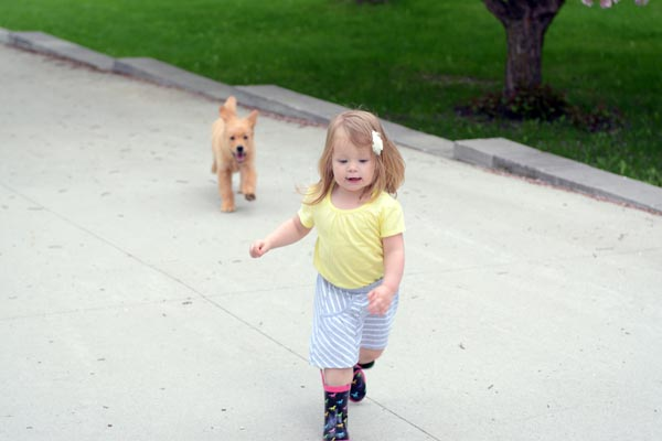 a little girl running in front of a puppy