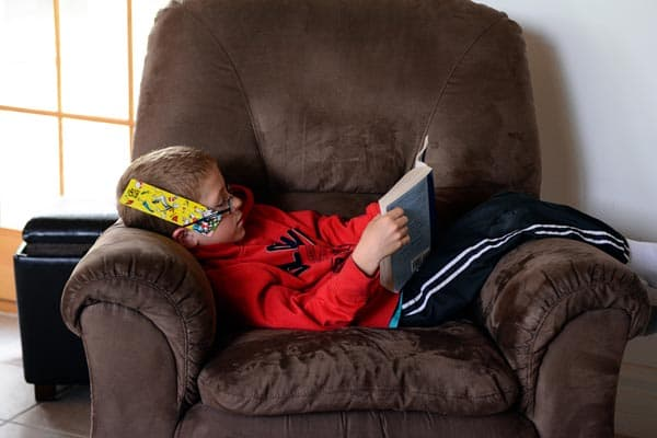 A little boy sitting on a brown recliner reading.