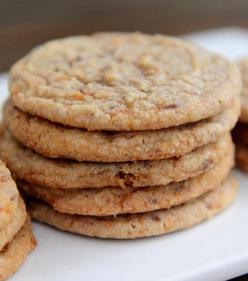 a stack of thin butterfinger cookies on a white plate