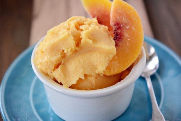 A small white bowl with fresh peach frozen yogurt and a few peach slices.