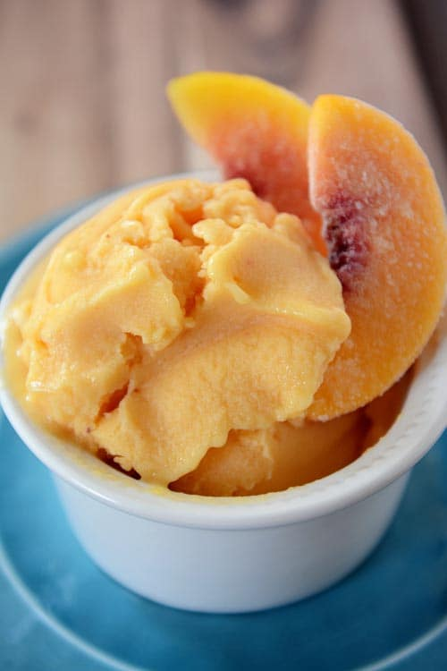 A small white ramekin with scoops of fresh peach frozen yogurt and a few frozen peach slices.