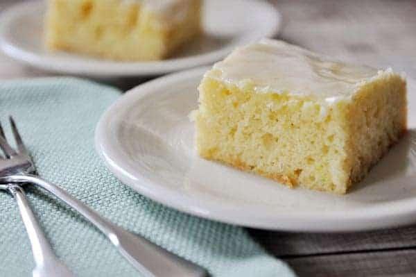 Two pieces of glazed lemon yogurt sheet cake on small white plates.