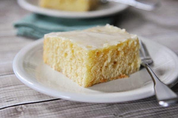 A square piece of glazed lemon sheet cake on a white plate.