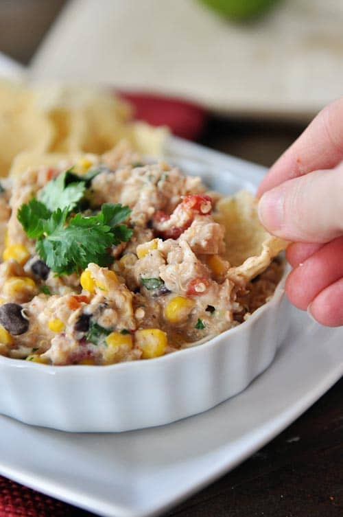 A tortilla chip being dipped into a white ramekin full of a creamy tex-mex mixture.