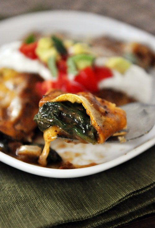 A bite of a spinach enchilada on a fork with the rest of the enchilada and toppings on a white plate below it.
