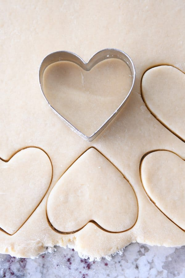 cutting out sugar cookie dough with heart cookie cutter