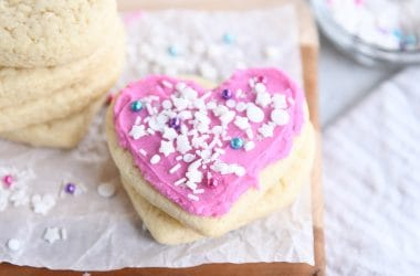 two sugar cookies with pink frosting and white sprinkles on parchment paper