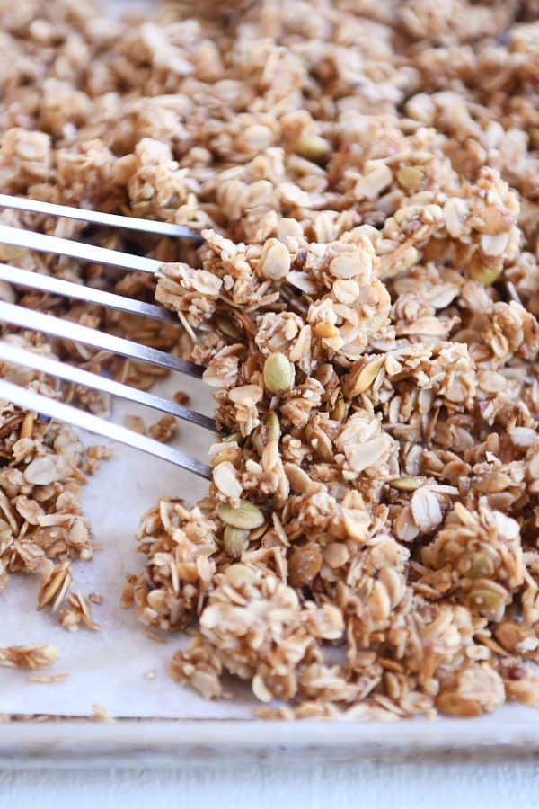 sheet pan with parchment and spatula sliding granola into a pile
