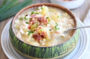 Green bowl filled with pressure cooker chicken corn chowder with bacon on top and spoon in the side.