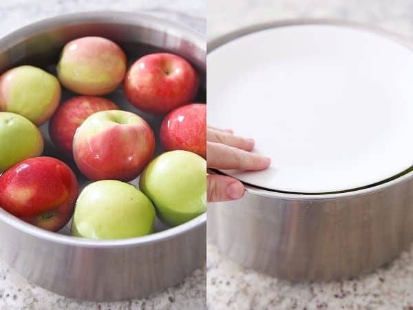Soaking washed apples in hot water in stainless pot.