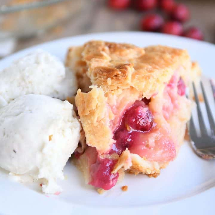 Slice of apple cranberry pie on white plate with ice cream.