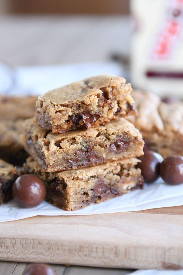 Two malted chocolate chip blondies stacked with half of a blondie on top.