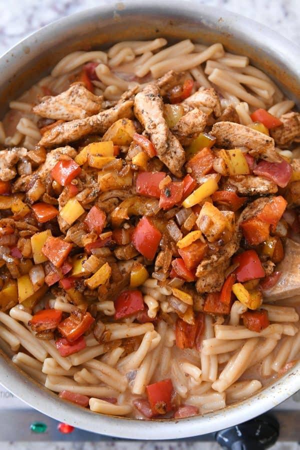 Combining skillet chicken fajita pasta.