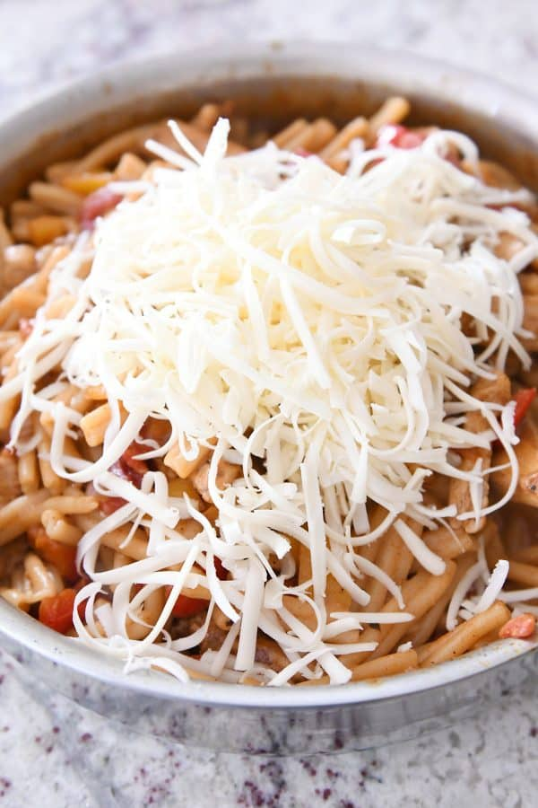 Adding cheese to skillet chicken fajita pasta.