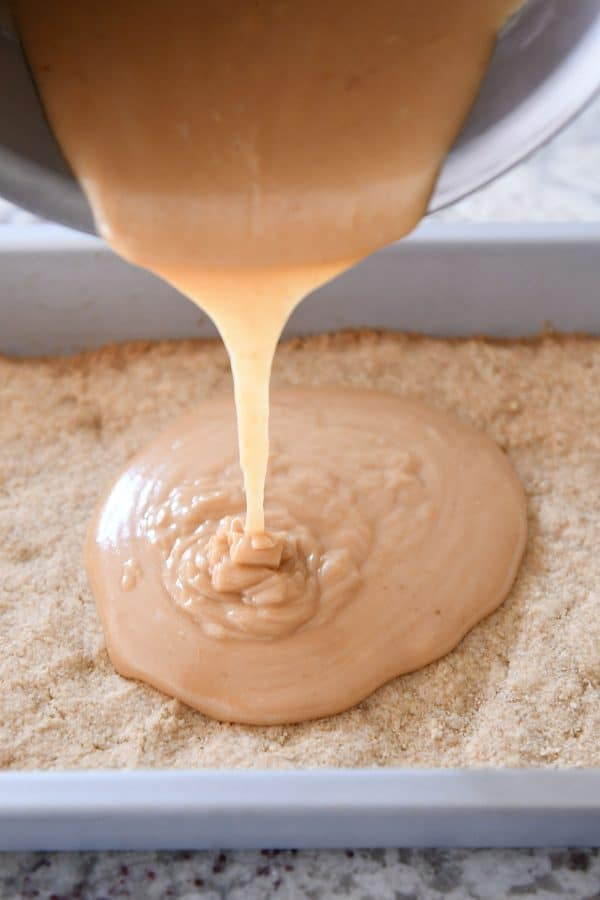 Pouring homemade caramel on top of shortbread crust