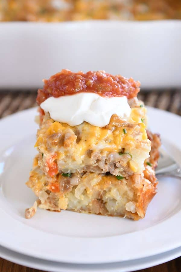 Two squares of tater tot breakfast casserole stacked on each other on white plate with sour cream and salsa.