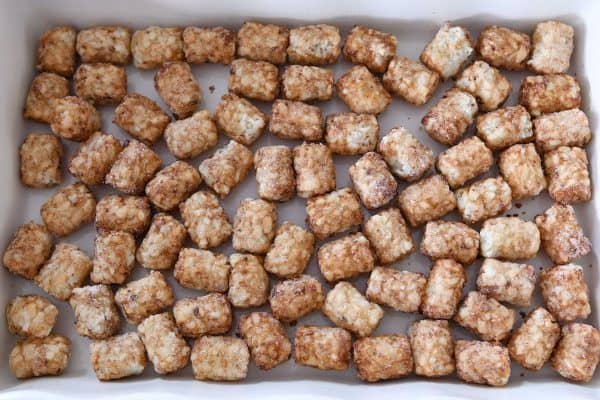 Tater tots scattered in bottom of 9X13-inch baking pan.