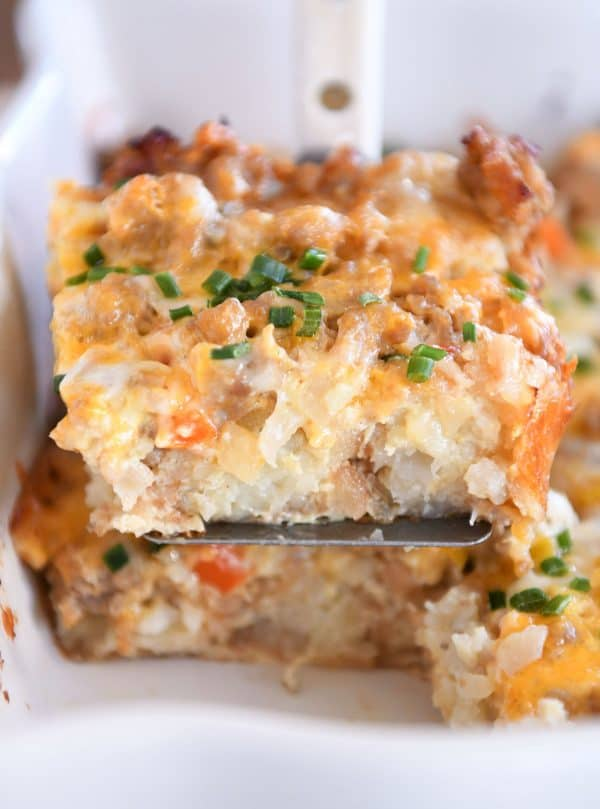 Square of tater tot breakfast casserole scooped on metal spatula.