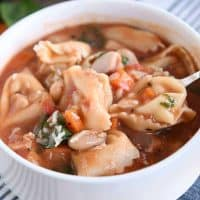 White bowl with handles filled with quick and easy creamy tuscan tortellini soup.