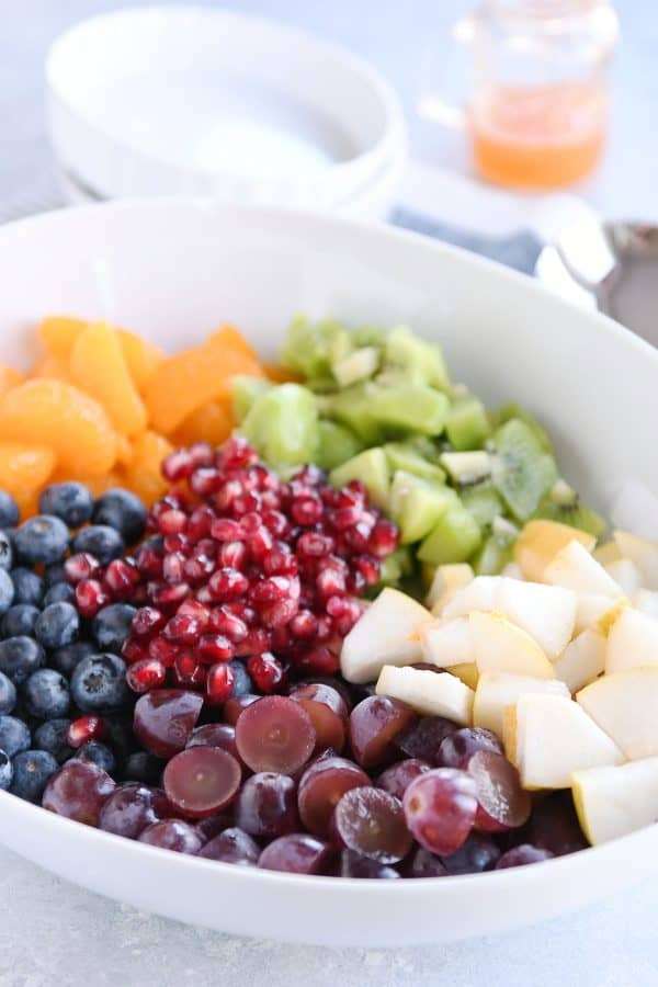 White bowl with grapes, blueberries, pears, kiwi, oranges and pomegranate seeds for easy winter fresh fruit salad.