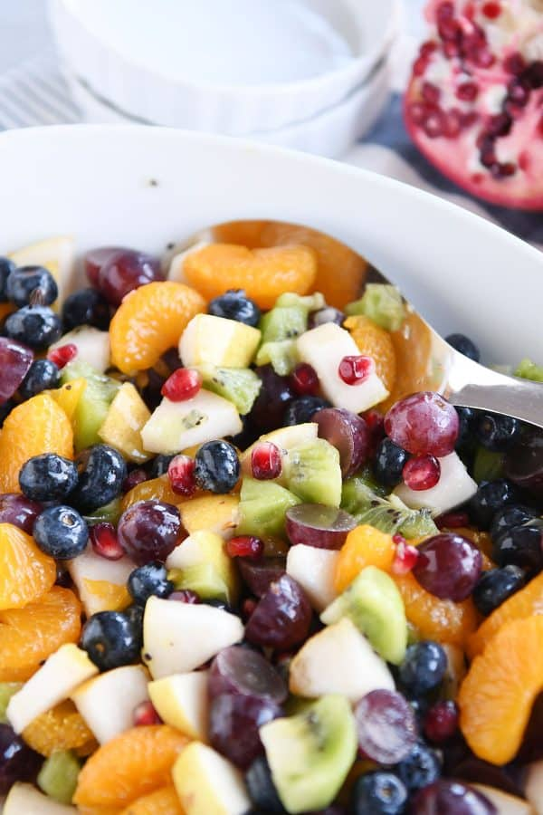 White bowl and spoon with grapes, blueberries, pears, kiwi, oranges and pomegranate seeds for easy winter fresh fruit salad.