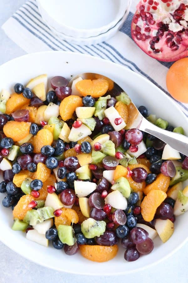 Top down view of white bowl with grapes, blueberries, pears, kiwi, oranges and pomegranate seeds for easy winter fresh fruit salad.