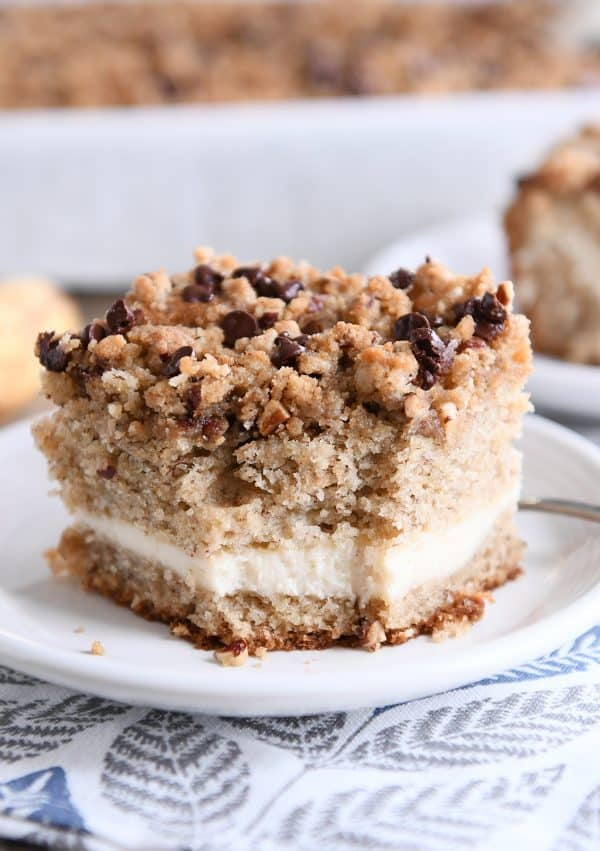 Piece of banana cream cheese coffee cake with chocolate chip streusel on white plate with bite taken out.