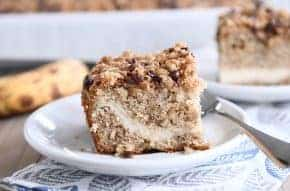 Piece of banana cream cheese coffee cake with chocolate chip streusel on white plate.