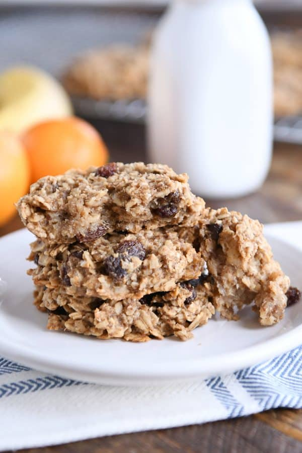 baked healthy breakfast cookies on white plate with one cookie broken in half