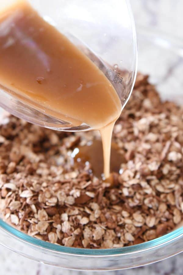 pouring syrup onto dark chocolate brownie granola bar ingredients