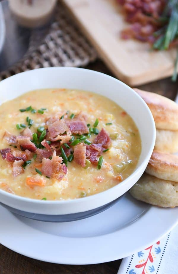 bowl of loaded cheesy cauliflower soup with rolls