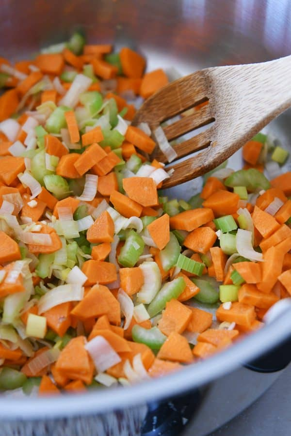cooking carrots, onions and celery for cheesy cauliflower soup