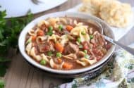 slow cooker beef vegetable noodle soup with spoon in gray ceramic bowl