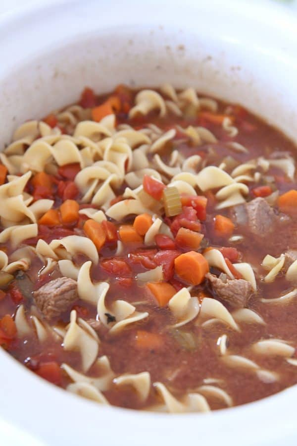 white slow cooker filled with beef vegetable noodle soup