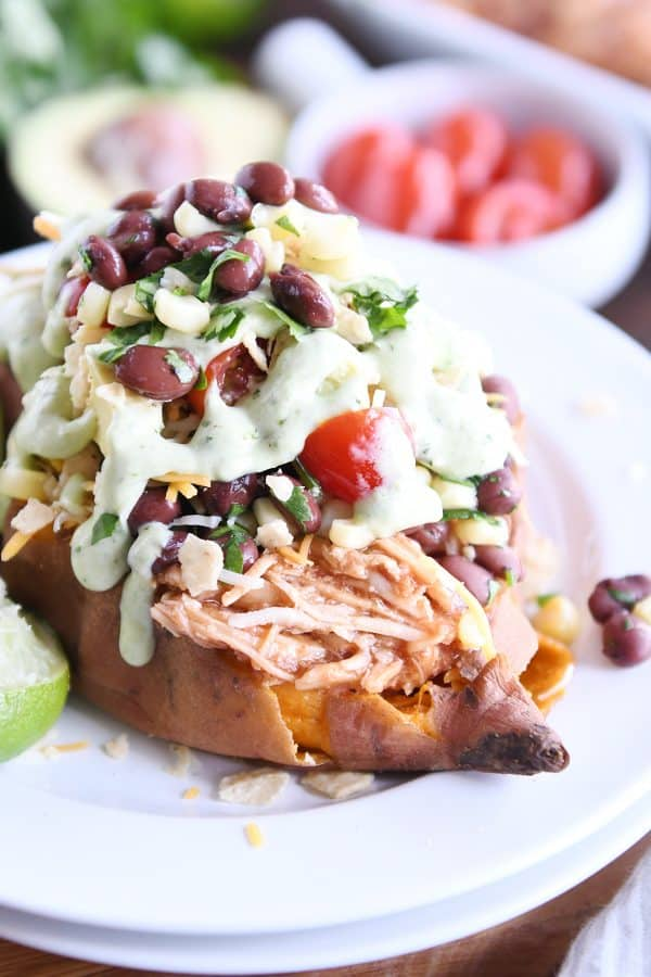 Loaded stuffed bbq chicken sweet potato with cilantro lime dressing on white plate