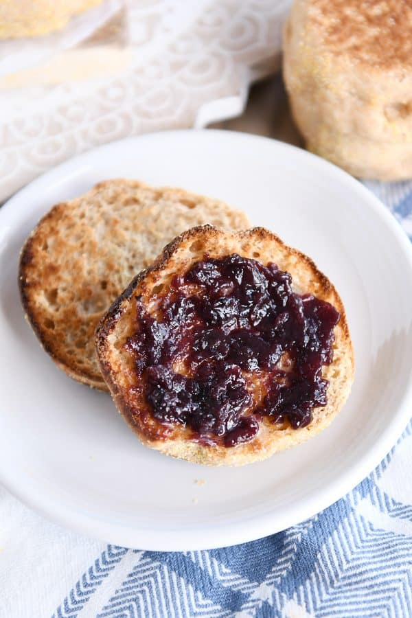 split open easy homemade english muffin with butter and jam on white plate