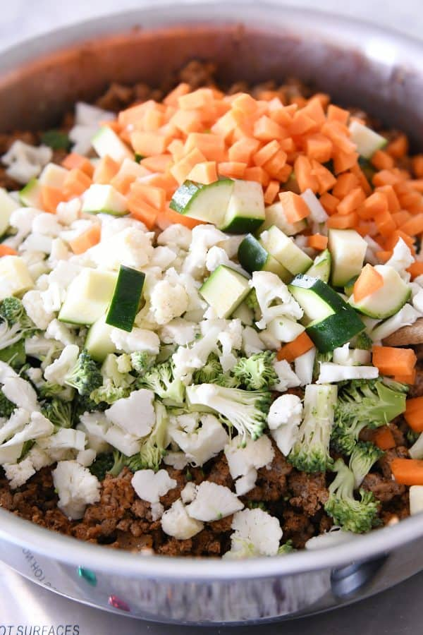 adding vegetables to taco filling