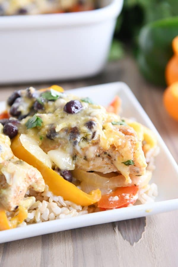 cheesy chicken enchilada bake over brown rice on white platter