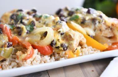 cheesy chicken enchilada bake over brown rice on white platter