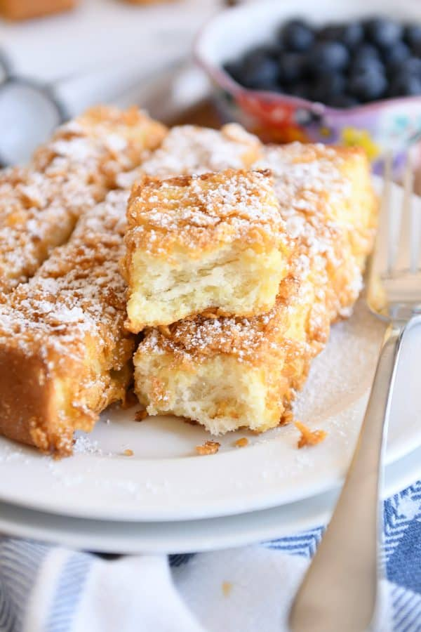 crunchy baked french toast sticks with powdered sugar on white plate